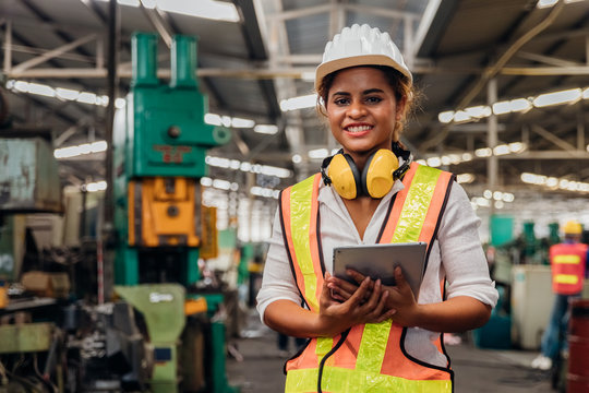 Industry maintenance engineer woman dark skin wearing uniform and safety helmet under inspection and checking production process on factory station by tablet. Industry, Engineer, construction concept.