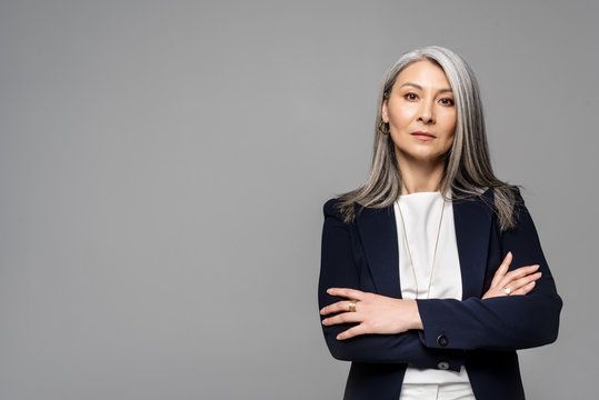 confident asian businesswoman with grey hair and crossed arms isolated on grey