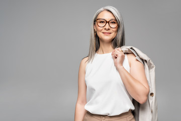 smiling asian businesswoman in eyeglasses isolated on grey