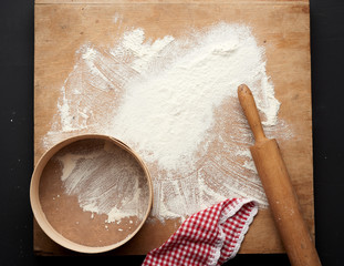 white wheat flour scattered on a black table and a wooden rolling pin, round sieve on a black table