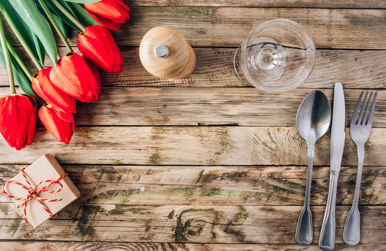 Spring rustic table setting with red tulip, glass and vintage cutlery on the wooden background.