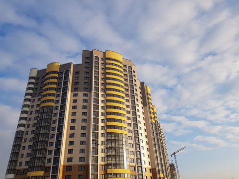Close-up of luxury high apartment complex. Fragment of modern residential flat exterior. Blue sky with clouds. Real estate property and posh architecture concept