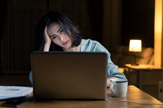 Asian woman work late from home in living room at late night overtime