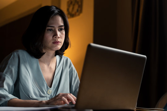 Asian business woman does overtime working from home in living room at late night due to covid19 pandemic. Girl feeling tired and serious face to complete jobs, looking and typing on conputer laptop.