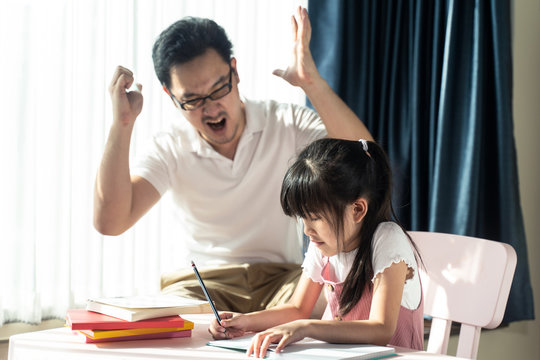 Homeschool Asian young little girl learning, reading and does homework with mean dad strictly  teaching encourage. Father angry  daughter that lazy to study hard. Family domestic parent, kid problem.