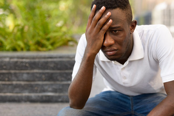 Portrait of stressed young African man looking depressed while sitting outdoors