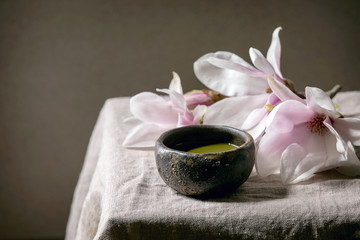 Japanese matcha green tea in wabi sabi ceramic cup with pink magnolia flowers on grey linen table cloth.