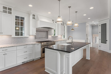 Kitchen in new luxury home with large island, pendant lights, hardwood floor and stainless steel appliances.