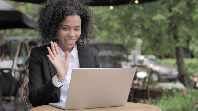 Video Chat by African Woman Sitting in Outdoor Cafe