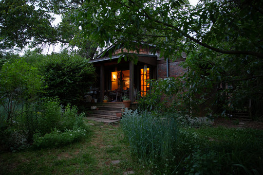 Cottage style home with garden at dusk