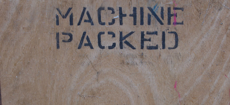 Old stencilled wooden sign in black lettering indicating machine packed