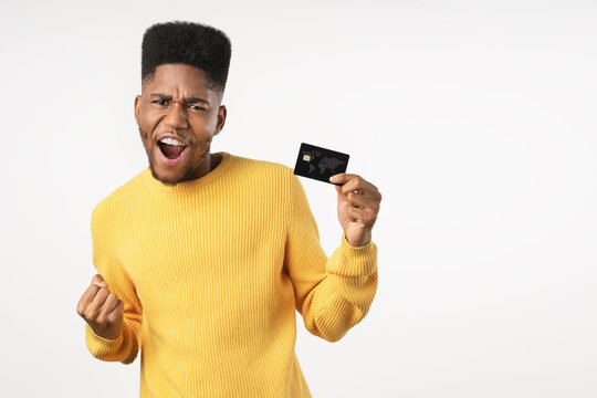 Afro american man holding credit card screaming proud and celebrating victory standing over isolated white background