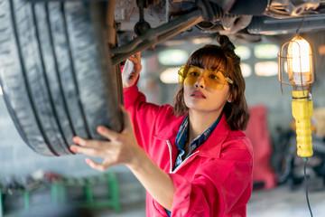 Woman Mechanic Examining Under the Car at the Repair Garage.