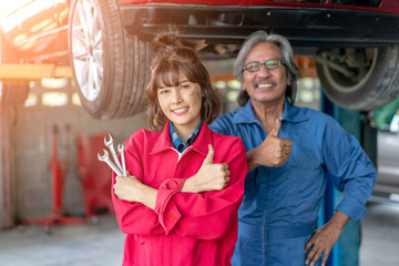 Team of Asian Mechanics Smiling and Giving Thumb Up.