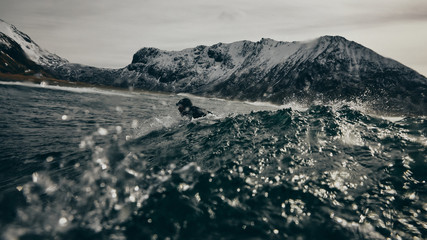Surfer paddles to catch a wave surrounded by mountains and snow