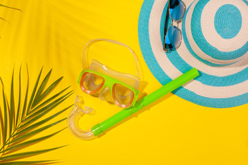 Top view on beach accessories on yellow background - sunglasses, striped blue hat, diving mask and palm leaf in palm leaf shadow. Concept of the long-awaited vacation at sea and travel. Advertising Wall mural