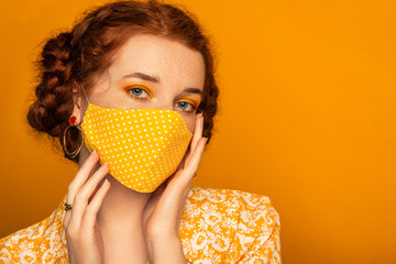 Woman wearing stylish handmade protective face mask posing on orange background.  Model with colorful eyes makeup. Fashion during quarantine of coronavirus outbreak. Copy, empty space for text