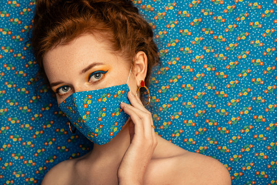 Woman wearing stylish handmade protective face mask posing on matching background of the same cloth. Model with blue eyelines makeup. Fashion during quarantine of coronavirus outbreak