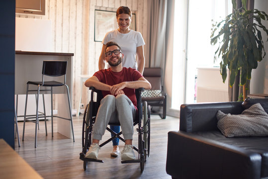 Woman pushing wheelchair with disabled man around the house