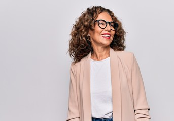 Middle age beautiful businesswoman wearing glasses standing over isolated white background looking to side, relax profile pose with natural face and confident smile.