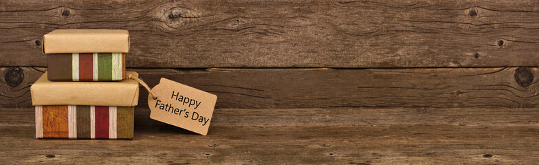 Happy Father's Day gift tag and two stacked boxes. Side view banner against a rustic brown wood background.