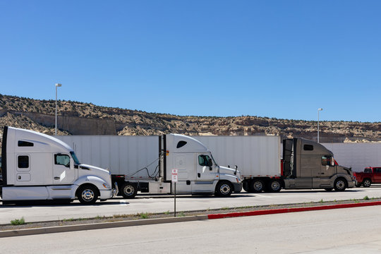 Three big rigs semi trucks of different brands models are lined up in parking lots truck stops or  rest areas filling vacant places to rest have lunch or wait for cargo according to log book.