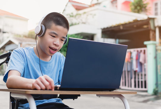 Special need child on wheelchair happy time to use a notebook in the house, Study and Work at home for safety from covid 19, Life in the education age of special need kid, Happy disabled boy concept.