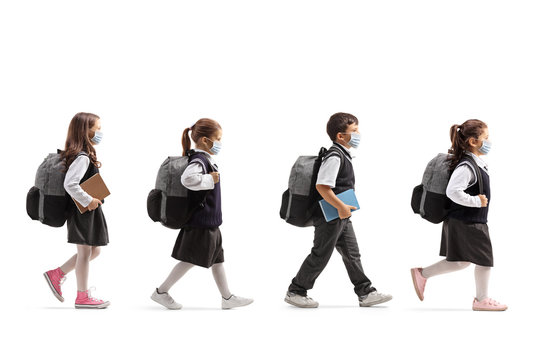 Schoolchildren in uniforms walking in line and wearing protective face masks