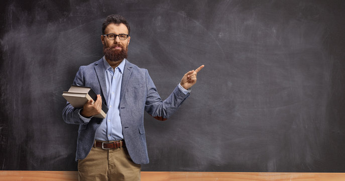 Male teacher holding books and pointing at a chalkboard