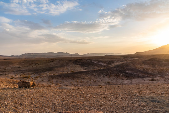 Beautiful dry landscape with colorful sand and cloudy blue sky. Sunset in the wilderness. The arid landscape of the prairie. Israel Negev Desert Sede Boker. Great view of the Nakhal Tsin rift.