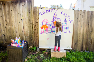A young girl painting a picture of a castle outside on the side of a fence.