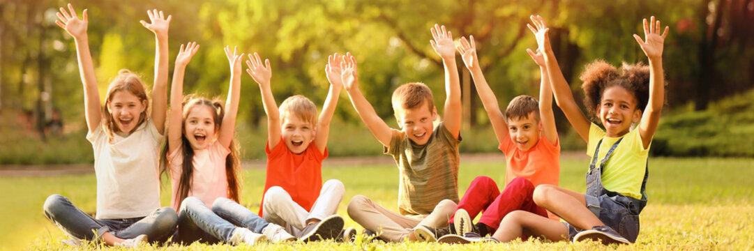 Cute little children sitting on grass outdoors on sunny day. Banner design