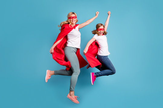 Full body photo of funny mom lady little daughter spend time together carnival super hero costumes jump high up raise fists wear s-shirts red coat masks isolated blue color background