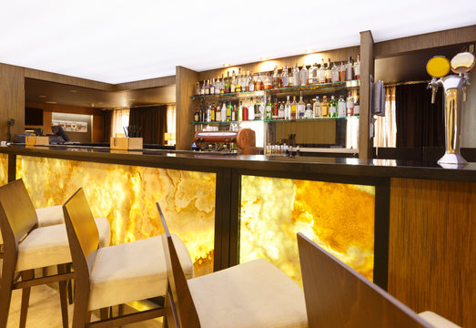 Futuristic hotel bar. Yellow-brown design with high chairs