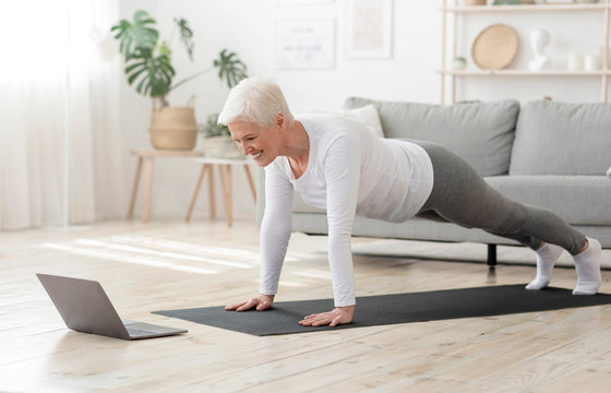 Active Senior Woman Making Plank In Front Of Laptop At Home