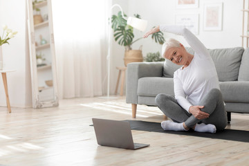 Happy senior woman doing stretching exercises in front of laptop at home