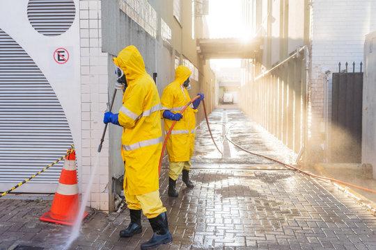 Homens de roupa de proteção amarela, fazendo a limpeza próximo aos hospitais, deivdo ao cornavirus.  Contribuem para a desinfecção das calçadas