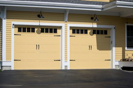 Two cars Garage Door painted in Yellow color in a typical single house