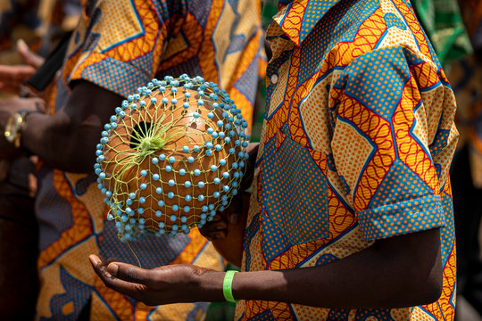 A closeup photo shows a drummer playing an African Shekere gourd percussion instrument while marching in a procession during a kente yam festival in Ghana, West Africa.