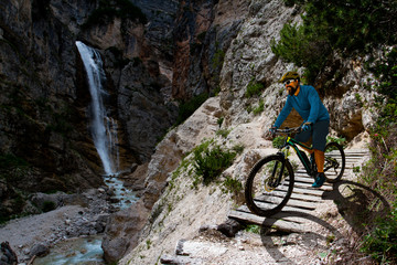 Wall Mural - Man cycling on electric bike, rides mountain trail. Man riding on bike in Dolomites mountains landscape. Cycling e-mtb enduro trail track. Outdoor sport activity.