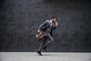 Young fashionable businessman running on the street. He is late for work.