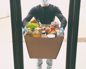 The courier is delivering the cardboard eco box with groceries from the supermarket wearing latex gloves and medical mask
