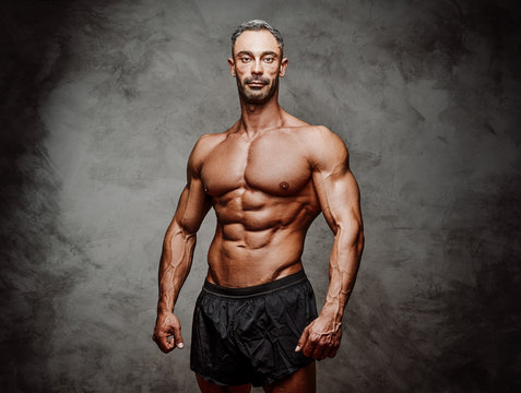 Shirtless adult male bodybuilder posing for a photoshoot shirtless in a dark studio