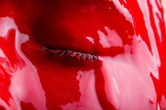Image of a girl's face with spreading glossy red paint