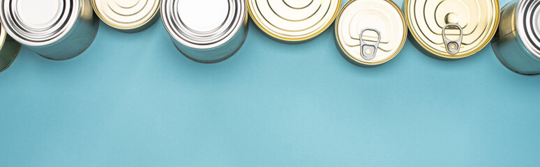 top view of cans on blue background with copy space, food donation concept