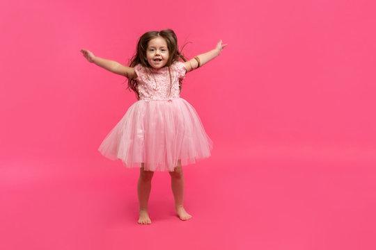 Cute little girl dreams of becoming a ballerina. Little Dancing Girl. Studio Shoot Over Pink Background