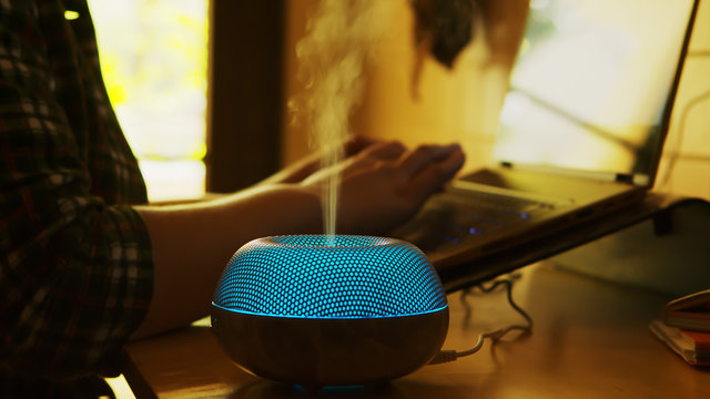 Silhouette of blue led essential oil diffuser steaming in a room with female entrepreneur working on laptop.
