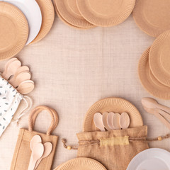 recycled paper disposable plates and eco friendly wooden spoon, table set, top view, beige color,...