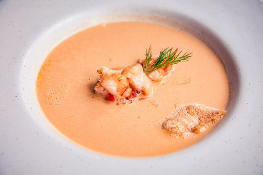 Closeup of creamy lobster bisque soup with grilled prawn and dill in white bowl