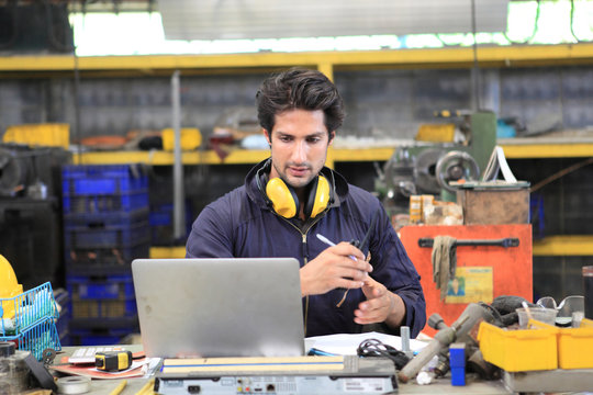 Factory Engineer use mobile phone contact to team for control in industry factory